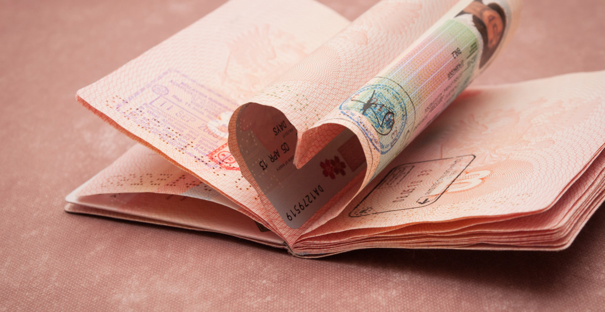Passport pages in shape of heart on pink background